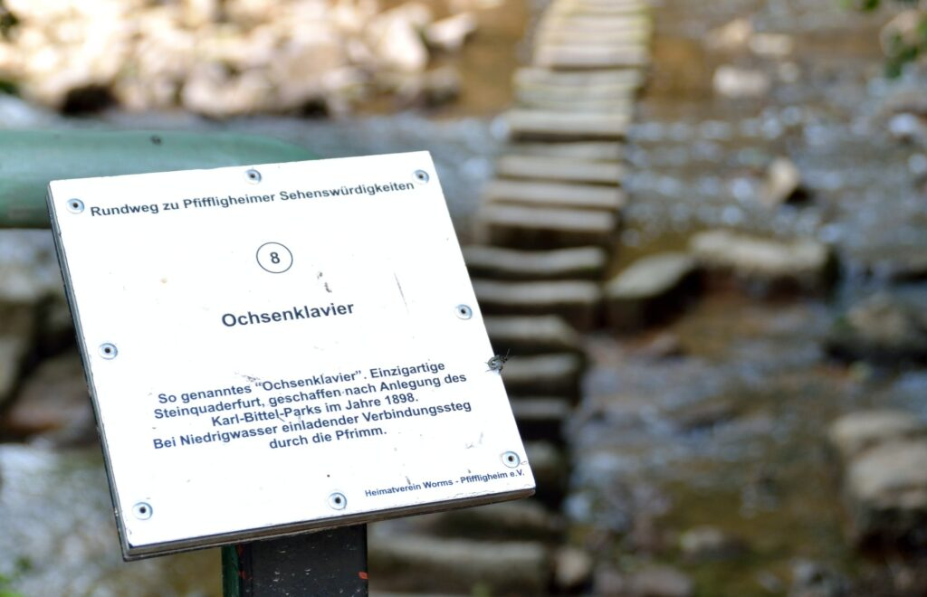 Ein Schild erklärt das Ochsenklavier im Pfrimmpark Worms